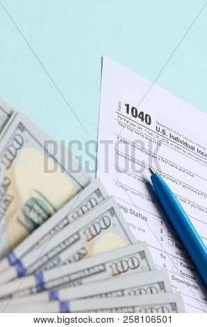 1040 Tax Form Lies Near Hundred Dollar Bills And Blue Pen On A Light Blue Background. Us Individual
