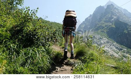 Woman Hiker Climbs Uphill With Phone In A Hiking Trip With Beautiful Scenery. Girl With A Backpack O