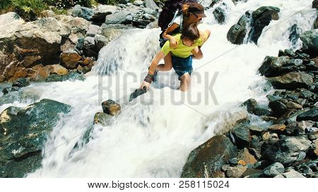 Man Carries A Woman With A Backpack Over A Mountain Stream On Her Back Barefoot Into A Ford. The Guy