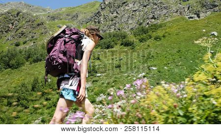 Tired Woman Hiker Climbs Uphill In A Hiking Trip With Beautiful Scenery. Girl With A Backpack On The