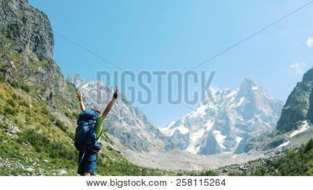 Man Goes Through The Route, Climbs Uphill And Raises His Hands Up After Climbing In The Hike, A Beau
