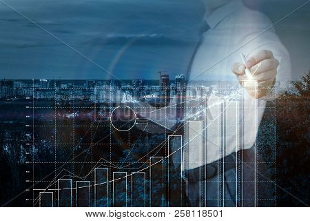 Businessman Draws A Graph Of Successful Growth Of Profits In The Backdrop Of The City.