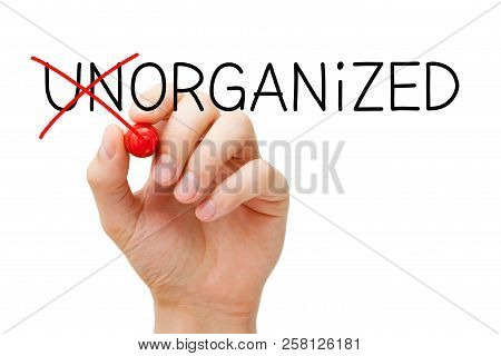 Hand Changing The Word Unorganized Into Organized With Red Marker Isolated On White.