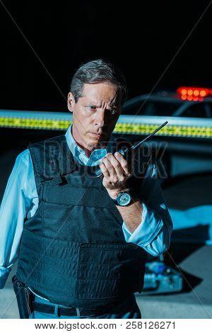 serious mature policeman in bulletproof vest talking on radio set near car at crime scene poster