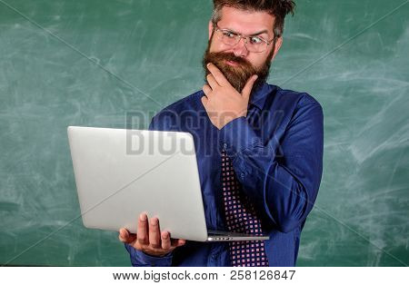 Distance education concept. Hipster teacher wear eyeglasses and necktie holds laptop surfing internet. Teacher bearded man with modern laptop surfing internet chalkboard background. Surfing internet poster