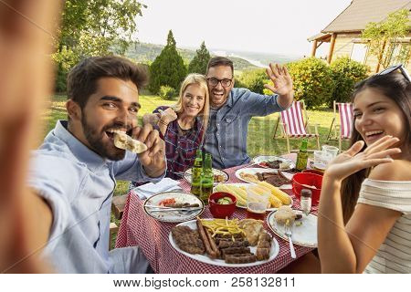 Group Of Friends Having A Backyard Barbecue Party, Having Fun Taking Selfies. Focus On The Couple In