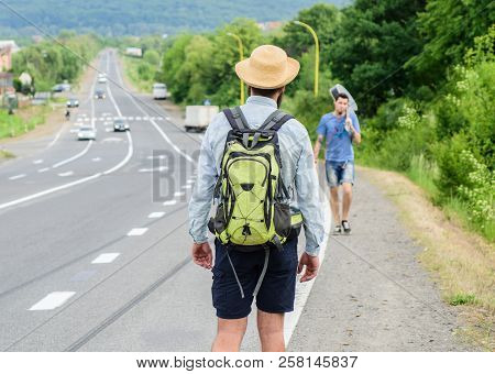 Meet fellow traveler. Man traveler hitchhiker meet companion at road edge. Friends or companions travelling by hitchhiking. Man with backpack wait for friend at edge of road. Start of journey poster
