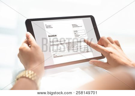 Businesswoman Checking Invoice On Digital Tablet