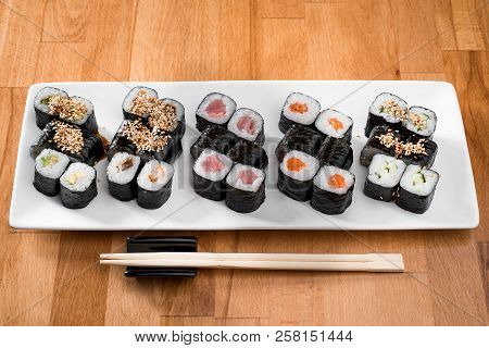 Maki Sushi Rolls With Salmon, Tuna, Eel And  Avocado On A White Plate. Close Up. Japanese Food Resta