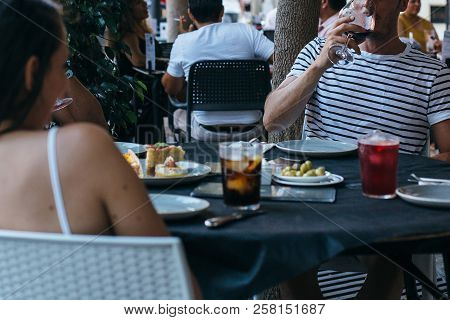 Cropped View Of A Couple Enjoying Free Time Drinking Beer And Tasting Spanish Tapas At The Bar Terra