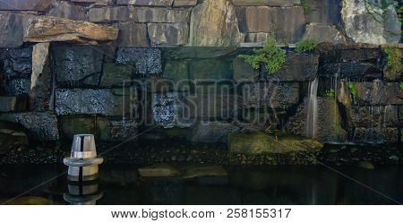 Small Waterfall Cascading Down Stone Wall Of Man Made Stream.