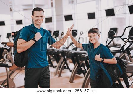 Young Father And Son Near Treadmills In Modern Gym. Healthy Lifestyle Concept. Sport And Training Co