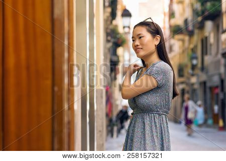 Chinese Woman Shopper Watching Offers In A Storefront.