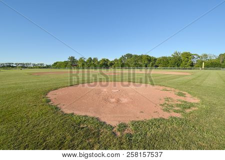 Baseball Field Diamond As Seen From Behind Home Plate In Summer Under A Clear Blue Sky With A Green