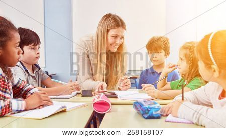 Group of children doing homework together with a teacher in a full-time school