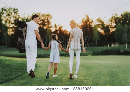 Happy Young Family Relax On Golf Field In Summer. Relaxing In Golf Club. Sports In Summer. Outdoor F