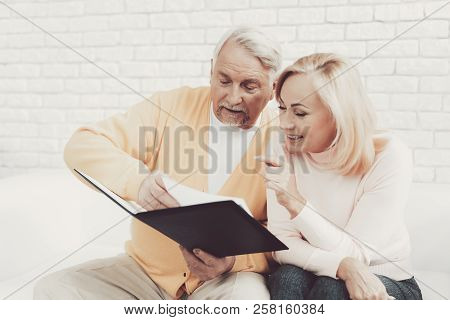 Old Man Near Old Woman With Documents In Black Folder. Important Documents. Sitting On White Sofa. G