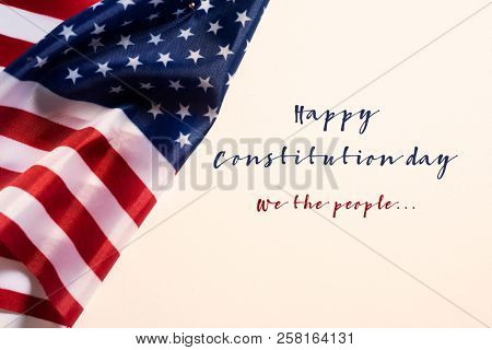 closeup of a flag of the United States and the text happy constitution day against an off-white background