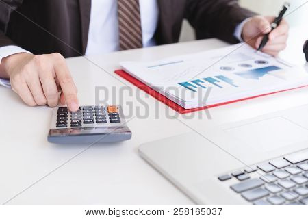 Male Accountant Using Calculator And Discussing Financial Reports.finance Accounting Concept
