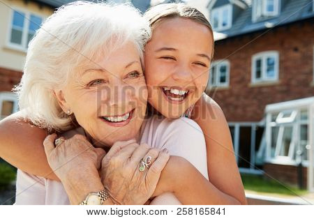 Granddaughter Hugging Grandmother On Bench During Visit To Retirement Home poster