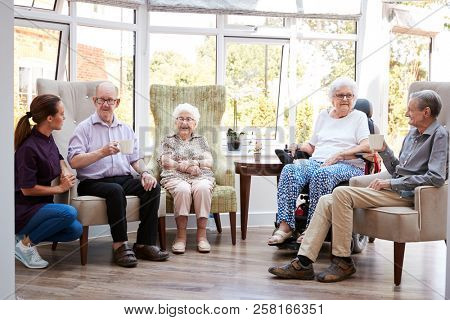 Portrait Of Excited Senior Woman Sitting In Chair In Lounge Of Retirement Home