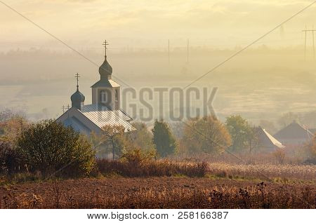 Orthodox Church On A Hill Above The Foggy Rural Valley At Sunrise. Lovely Countryside Scenery In Aut