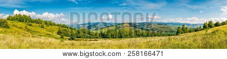 Autumnal Panorama Of Mountainous Countryside. Grassy Meadow On A Slope. Rural Fields On The  Hill In