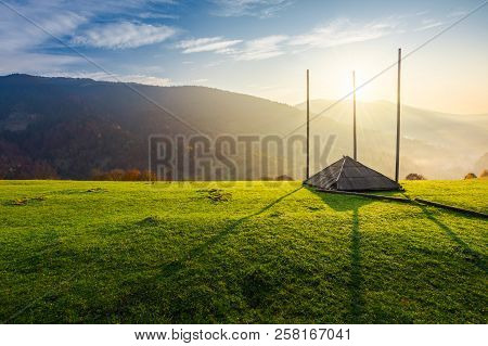 Empty Hay Barrack On A Grassy Hill At Sunrise. Beautiful Foggy Scenery In The Distant Valley. Rural