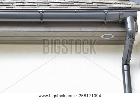 Grey plastic rain gutter with drain downspout pipe installed on asphalt shingles roof wooden eaves with round ventilation grille with copy space for text on white facade. Home improvement concept. poster
