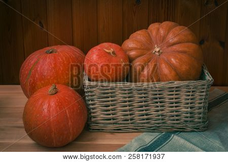 Different Pumpkins In Wicker Basket And Near
