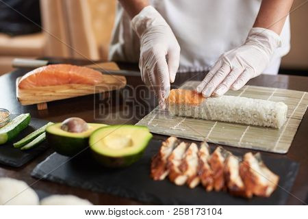 Closeup Viev Of Chef Hands Preparing Japanese Food. Chef Making Sushi Rolls At Restaurant With Many
