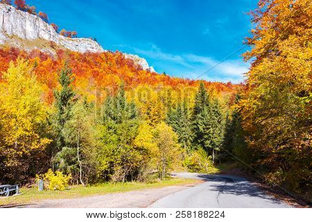 Road Through Gorgeous Serpentine In Autumn Forest. Huge Rocky Formation On The Hill Above The Path.