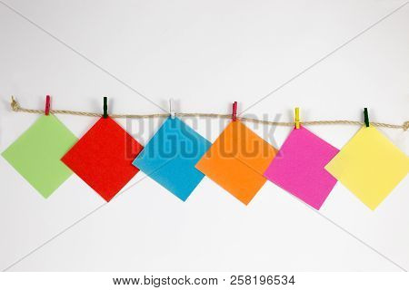 Post-it Notes With Small Colored Pegs In A Rope In White Background