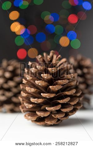Round Conifer Cones With Defocused Colorful Christmas Tree Bokeh Lights. Vertical Orientation.