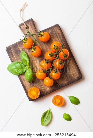 Organic Cherry Orange Rapture Tomatoes On The Vine With Basil On Chopping Board On White Background.