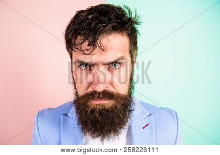 Hipster guy with messy tousled hair and long beard needs barber service. Keep hair tidy and care about hairstyle. Man bearded hipster on strict face pink blue background. Barber tips grooming beard poster