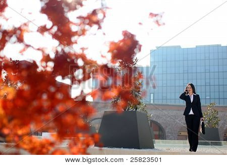 Business Woman Walking In Front Of A Corporate Building