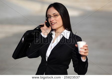 Buiness Woman Talking On The Phone And Holding Coffee