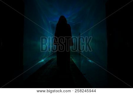 Creepy Silhouette In The Dark Abandoned Building. Dark Corridor With Cabinet Doors And Lights With S