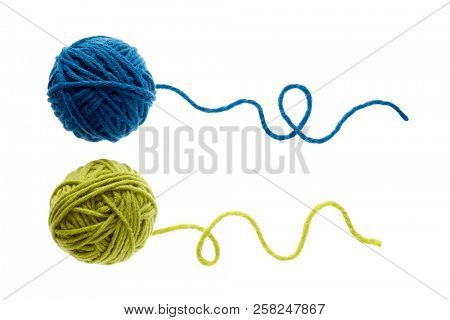Blue and green woolen balls over white background. Two balls of wool partially unrolled.