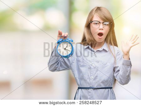Young blonde child holding alarm clock very happy and excited, winner expression celebrating victory screaming with big smile and raised hands