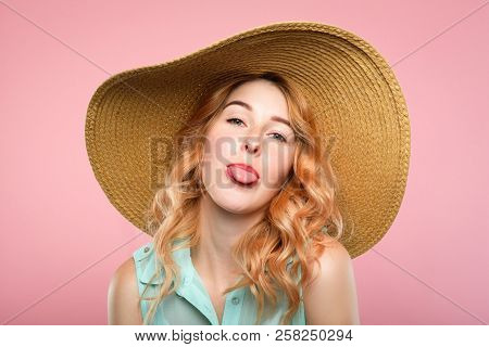 female naughtiness. cute antics and frolicking concept. mischievous childish behavior. portrait of a young beautiful girl sticking her tongue out. pretty woman in big sunhat on pink background. poster