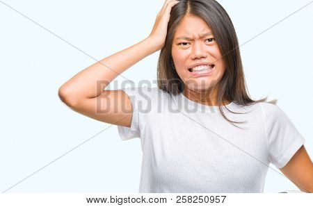 Young asian woman holding football soccer ball over isolated background stressed with hand on head, shocked with shame and surprise face, angry and frustrated. Fear and upset for mistake.