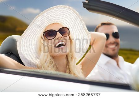 road trip, travel and people concept - happy couple driving in convertible car outdoors over big sur coast of california background