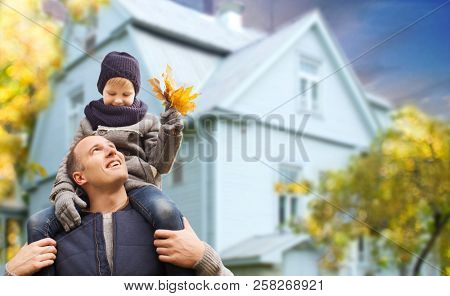 family, real estate and fatherhood concept - happy father carrying son with autumn maple leaves over living house background