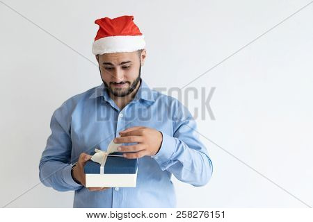 Excited Christmas Guy Unpacking Gift Box. Surprised Man In Santa Cap Ready To Open Christmas Present