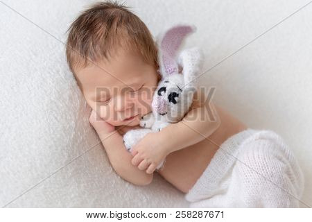 Little cute baby in white knitted pants holding white toy bunny and sleeping on white soft bedcover