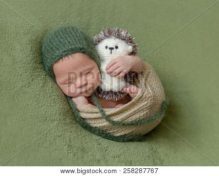 Little baby in dark green knitted beanie covered in lilac blanket sweetly sleeping on the soft green bedcover
