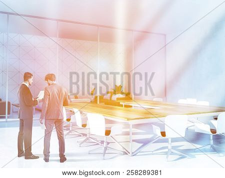 Two Businessmen Talking In White Triangular Tiled Boardroom With Panoramic Window, And Wooden Table