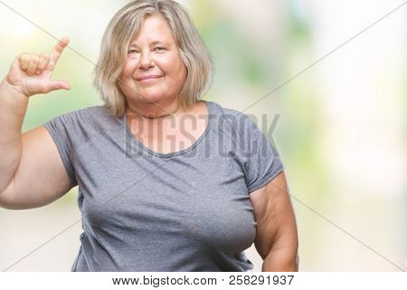Senior plus size caucasian woman over isolated background smiling and confident gesturing with hand doing size sign with fingers while looking and the camera. Measure concept.